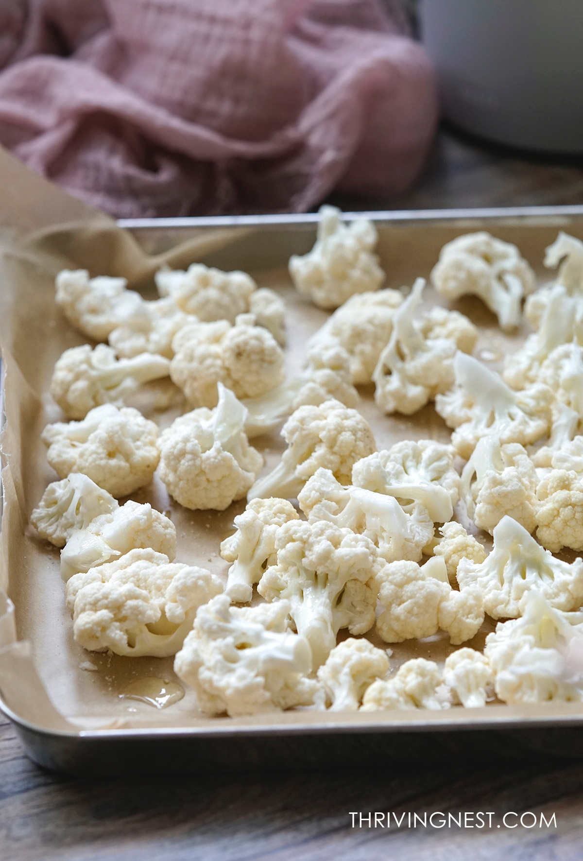 Prepared cut cauliflower florets placed in a baking sheet ready to be baked.