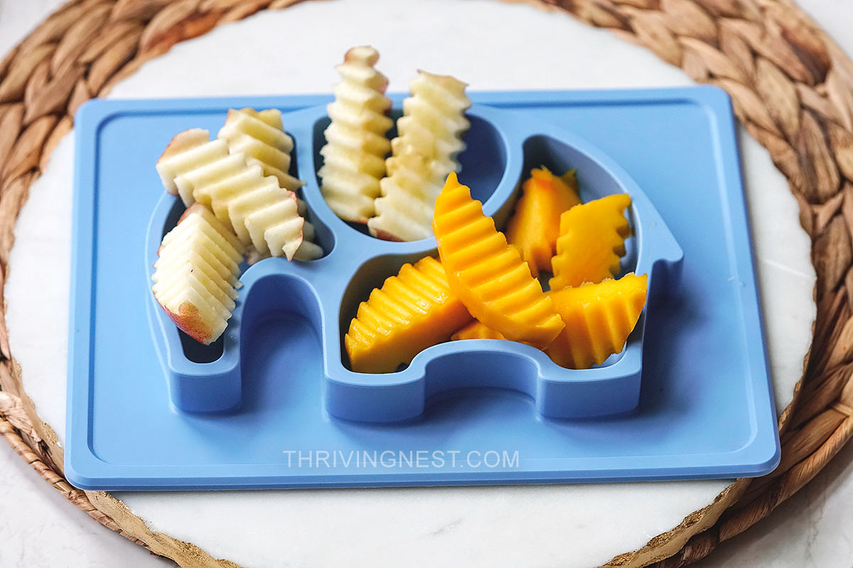 Baby led weaning first foods: mango apple cut into wedges or strips with a crinkle cutter.